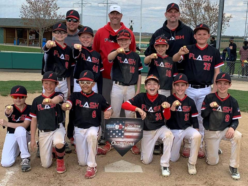 11U Flash baseball team with coaches wearing championship rings holding a home plate for Line Drive tournament