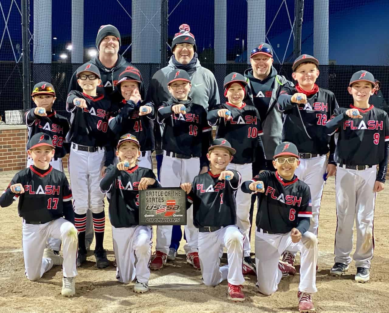 11 U boys Flash baseball team with coaches kneeling wearing rings and holding a championship plate for Battle of the States USSSA