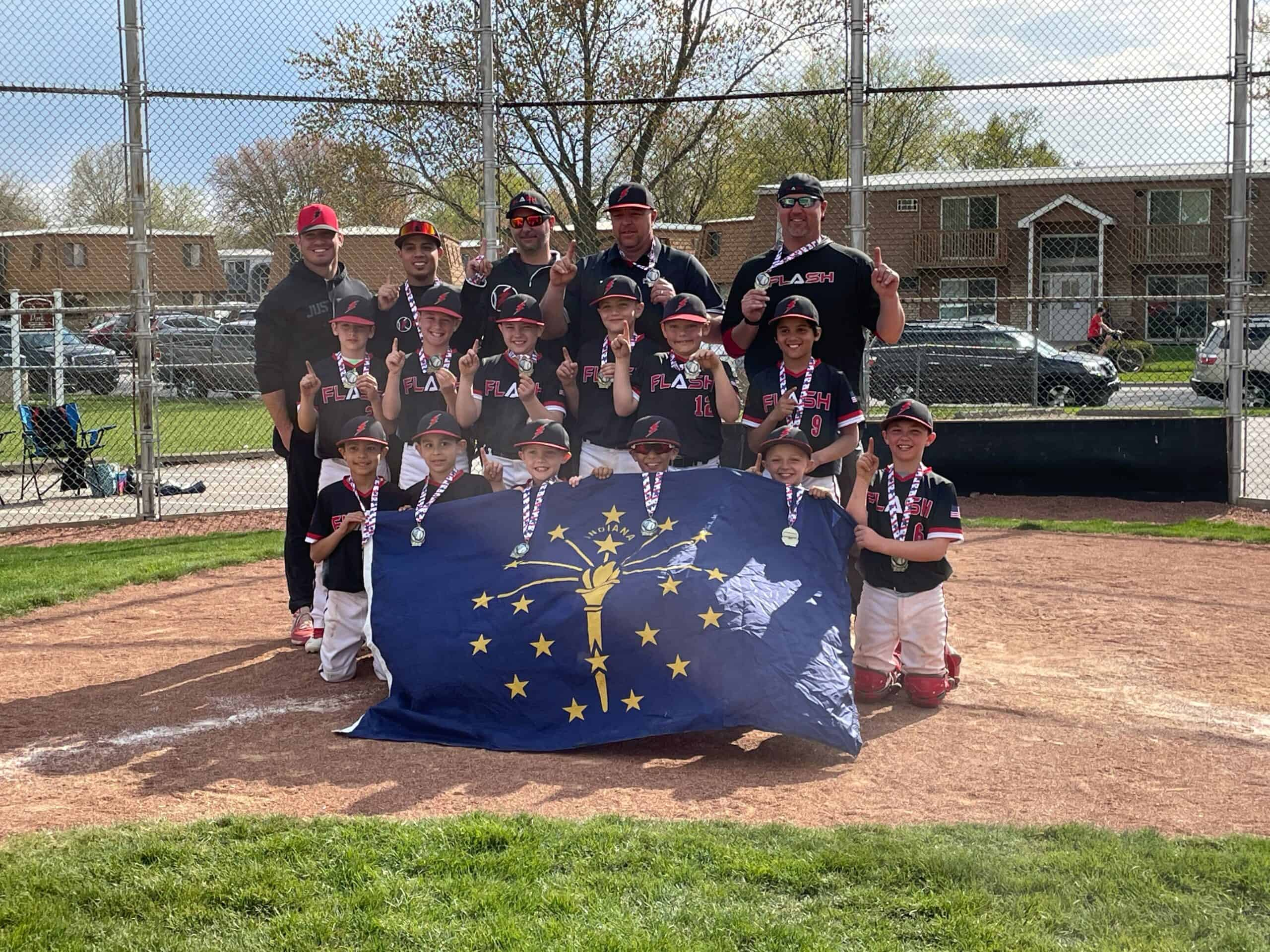 9U Flash Champions baseball team holding a banner wearing championship medals for Line Drive tournament