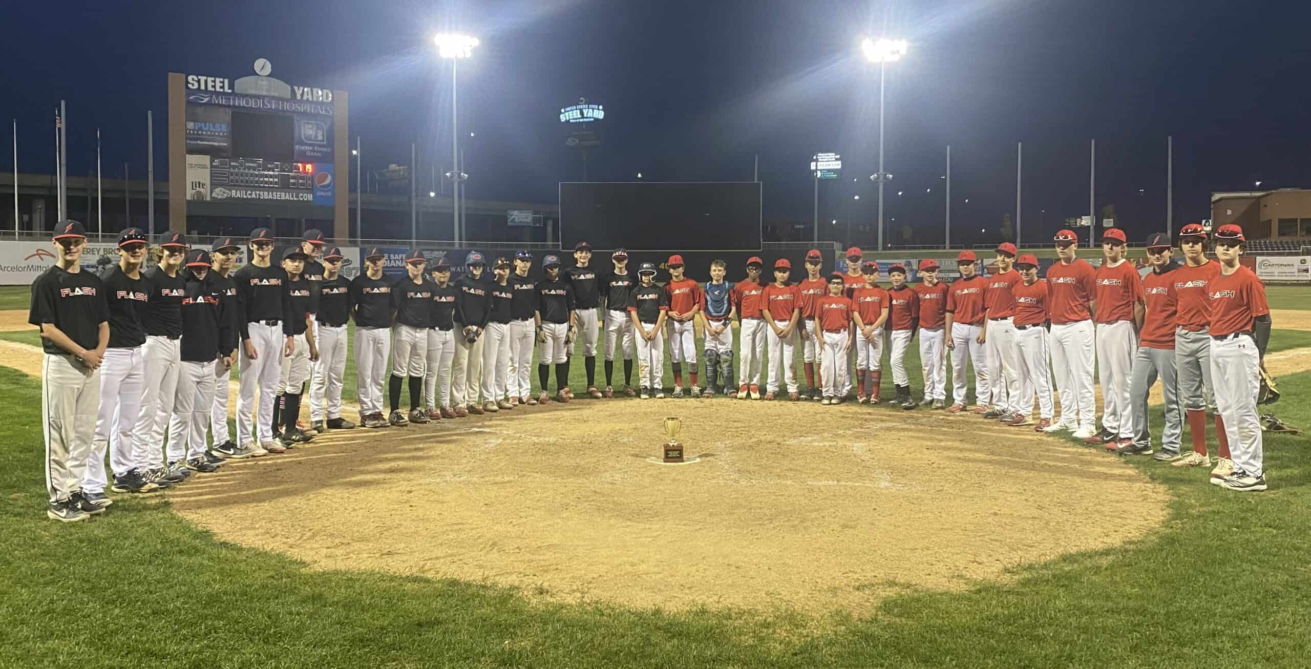 Flash red and black baseball teams standing around the trophy cup on a baseball field