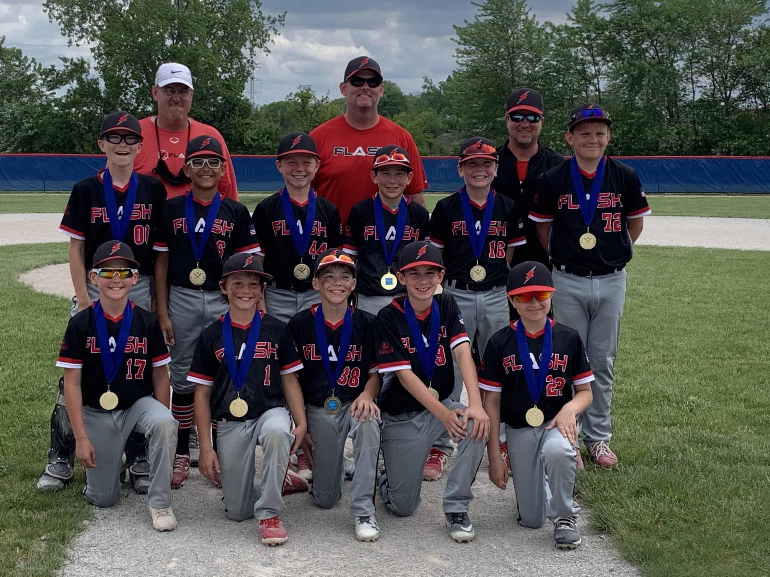 11 U boys Flash baseball team and coaches kneeling for Ho Chunk Slamfest wearing championship medals