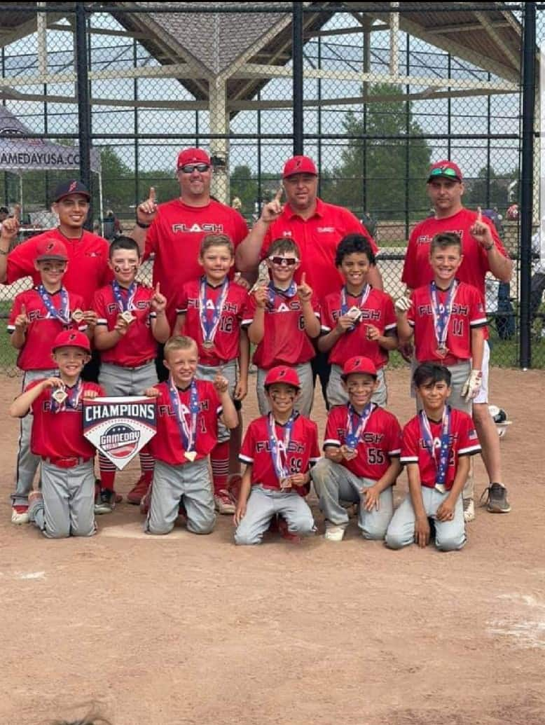 9U boys flash baseball team with coaches wearing championship medals and holding a champion home plate for Game Day tournament