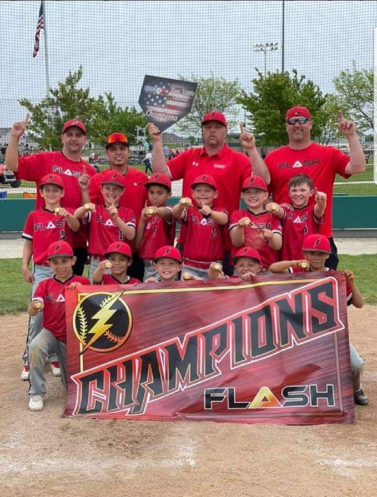 9U boys Flash baseball team holding a champions banner for the Ron Kittle Classic tournament